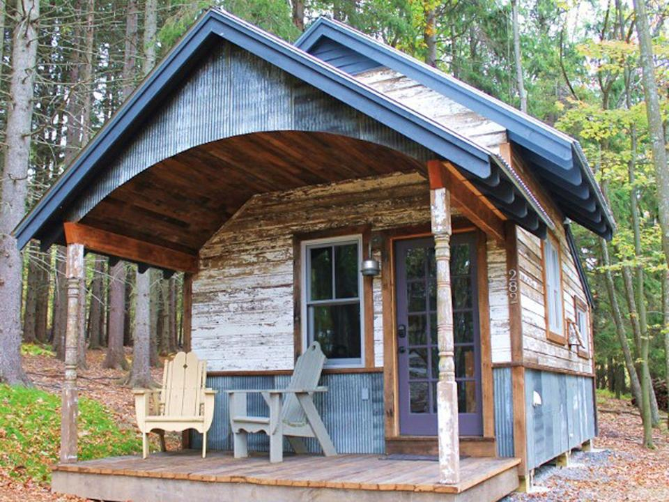 """<p>One of 14 tiny cabins at the <a href=""""https://bluemoonrising.org/"""" rel=""""nofollow noopener"""" target=""""_blank"""" data-ylk=""""slk:Blue Moon Rising ecotourism retreat"""" class=""""link rapid-noclick-resp"""">Blue Moon Rising ecotourism retreat</a> in McHenry, Maryland, the 250-square foot Kaya has a rustic reclaimed metal and wood exterior. Built by the folks at <a href=""""http://www.hobbitatspaces.com"""" rel=""""nofollow noopener"""" target=""""_blank"""" data-ylk=""""slk:Hobbitat"""" class=""""link rapid-noclick-resp"""">Hobbitat</a>, the quaint interior features a living space, queen-bed nook, bathroom, and kitchen with a view of nature, all under a curved, corrugated metal ceiling. Rental rates per night range from $249 to $349.<br></p><p><a class=""""link rapid-noclick-resp"""" href=""""https://go.redirectingat.com?id=74968X1596630&url=https%3A%2F%2Fwww.tripadvisor.com%2FHotel_Review-g41261-d5535285-Reviews-Blue_Moon_Rising-McHenry_Garrett_County_Maryland.html&sref=https%3A%2F%2Fwww.countryliving.com%2Fhome-design%2Fg1887%2Ftiny-house%2F"""" rel=""""nofollow noopener"""" target=""""_blank"""" data-ylk=""""slk:PLAN YOUR TRIP"""">PLAN YOUR TRIP</a> <a class=""""link rapid-noclick-resp"""" href=""""https://bluemoonrising.org/cabin-rentals/kaya/"""" rel=""""nofollow noopener"""" target=""""_blank"""" data-ylk=""""slk:SEE INSIDE"""">SEE INSIDE</a></p>"""
