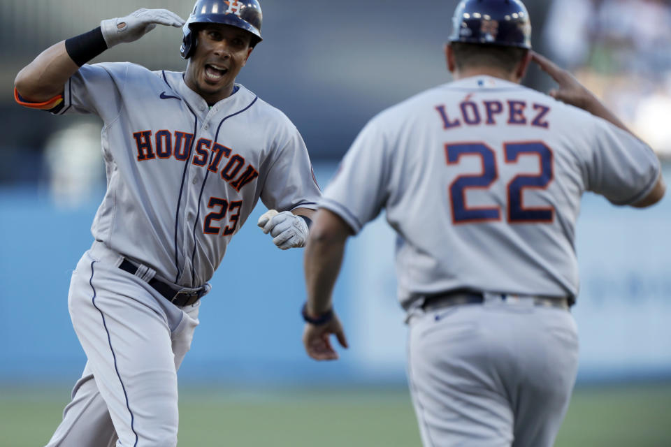 Houston Astros' Michael Brantley, left, celebrates with third base coach Omar Lopez while rounding the bases after hitting a solo home run against the Los Angeles Dodgers during the first inning of a baseball game in Los Angeles, Wednesday, Aug. 4, 2021. (AP Photo/Alex Gallardo)