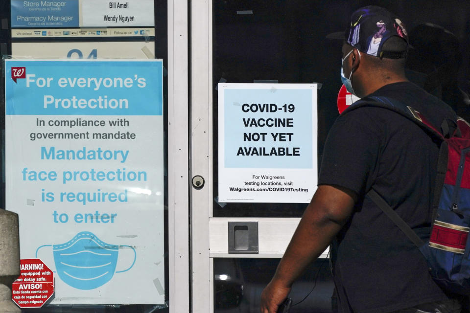 FILE - In this Dec. 2, 2020, file photo, a customer walks past a sign indicating that a COVID-19 vaccine is not yet available at Walgreens in Long Beach, Calif. (AP Photo/Ashley Landis, File)