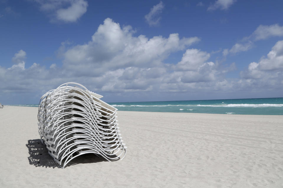 FILE - In this March 19, 2020 file photo, beach chairs sit on on an empty beach in Miami Beach, Fla. Reaction to the coronavirus, change came to the United States during the third week of March in 2020. It did not come immediately, though it came quite quickly. There was no explosion, no invasion other than a microscopic one that nobody could see. (AP Photo/Lynne Sladky, File)
