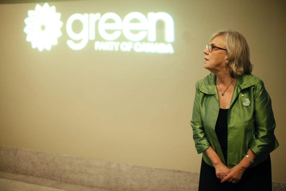 May stands in front of a Green Party sign, wearing a green jacket.