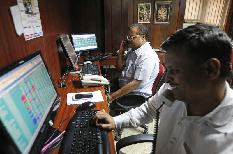 Brokers trade at their computer terminals at a stock brokerage firm in Mumbai