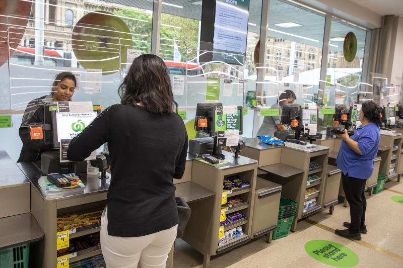 Photo shows Woolworths staff and customers interacting through a screen.