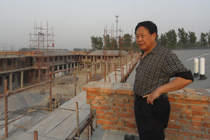 In this May 5, 2012, photo provided by the Legal Team of Dawu Group, Sun Dawu stands at a construction site for Dawu Town in Baoding in northern China's Hebei Province. A prominent Chinese pig farmer who was detained after praising lawyers during a crackdown on legal activists by President Xi Jinping's government has been sentenced to 18 years in prison on charges of organizing an attack on officials and other offenses. (Legal Team of Dawu Group via AP)