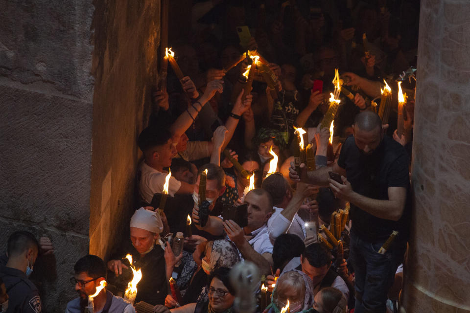 Christian pilgrims hold candles as they gather during the ceremony of the Holy Fire at Church of the Holy Sepulchre, where many Christians believe Jesus was crucified, buried and rose from the dead, in the Old City of Jerusalem, Saturday, May 1, 2021. Hundreds of Christian worshippers took use of Israel's easing of coronavirus restrictions Saturday and packed a Jerusalem church revered as the site of Jesus' crucifixion and resurrection for an ancient fire ceremony ahead of Orthodox Easter. (AP Photo/Ariel Schalit)