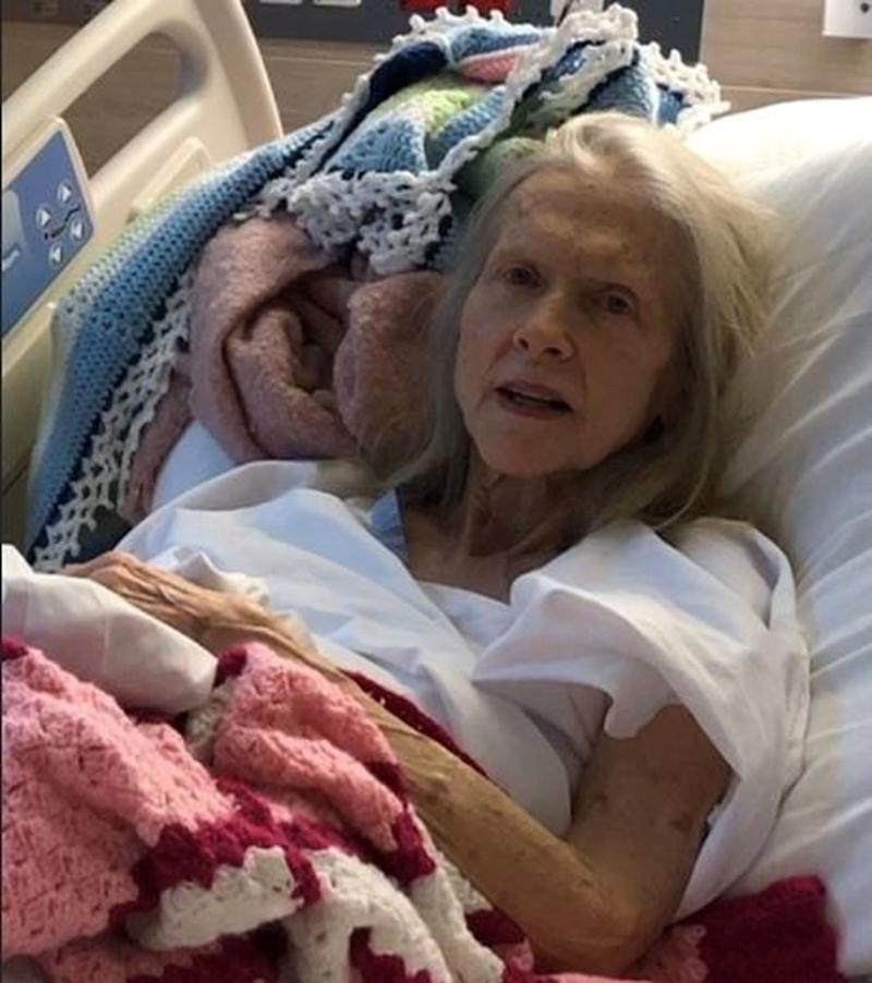 An elderly woman is pictured lying in a hospital bed. A search for her family is underway after she was picked up by a driver on the side of a Queensland road two weeks ago.