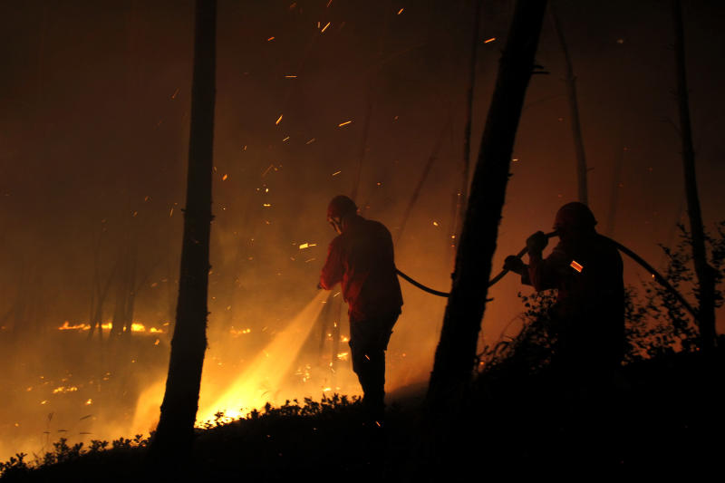 Firefighters work douse the fire in Ribeira do Farrio, near Ourem, Portugal, Monday, Sept. 3, 2012. A Portuguese official says authorities have asked other European countries to send help as the country's firefighters struggle to contain forest blazes being fueled by high temperatures and strong winds. (AP Photo/Francisco Seco)