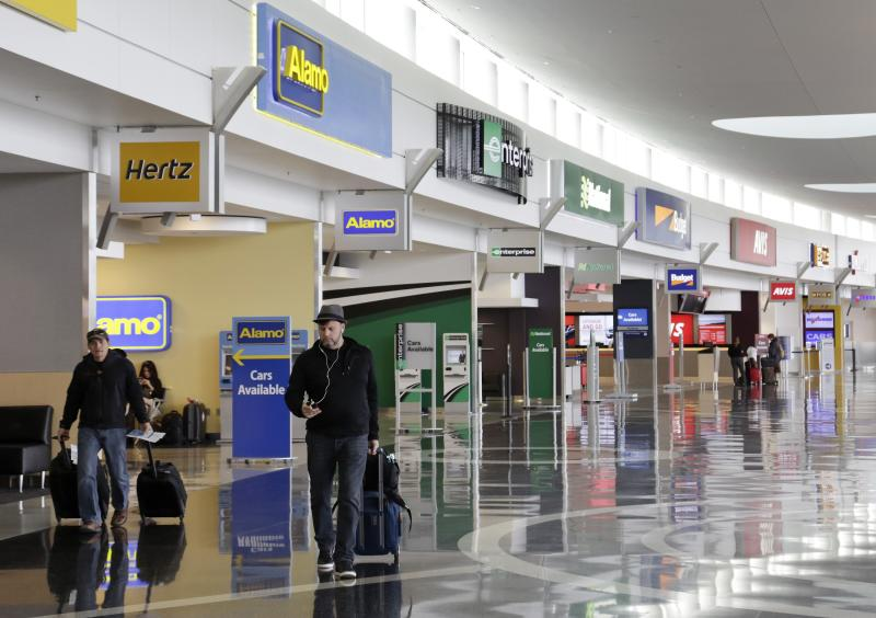 Travelers walk past rental car companies at Seattle-Tacoma International Airport