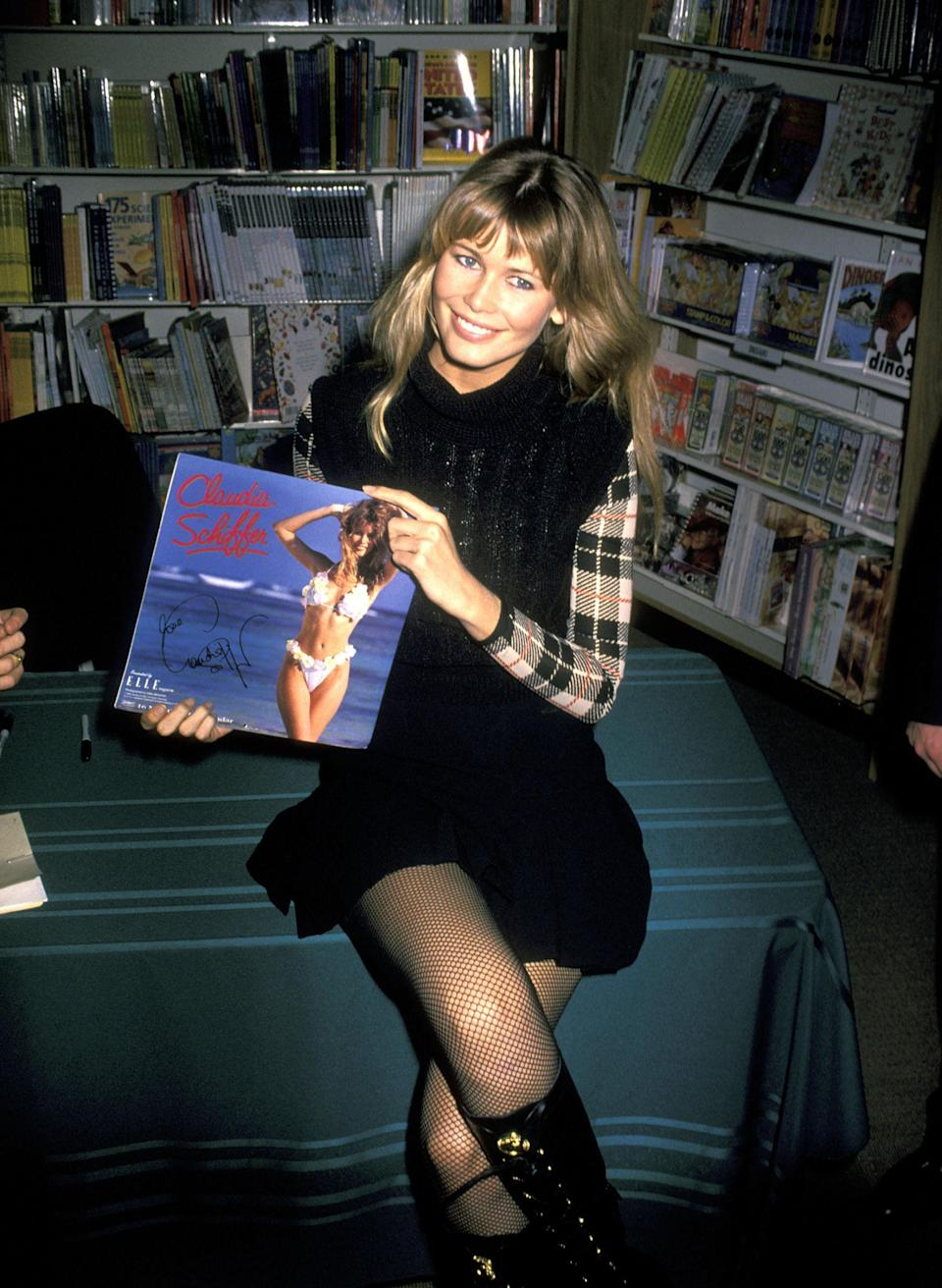<p>Claudia wears thigh-high boots and a plaid shirt a swimsuit calendar store promotion, 1994</p>
