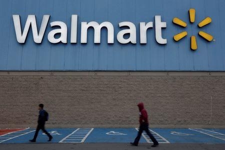 FILE PHOTO: Men walk past the logo of Walmart outside a store in Monterrey