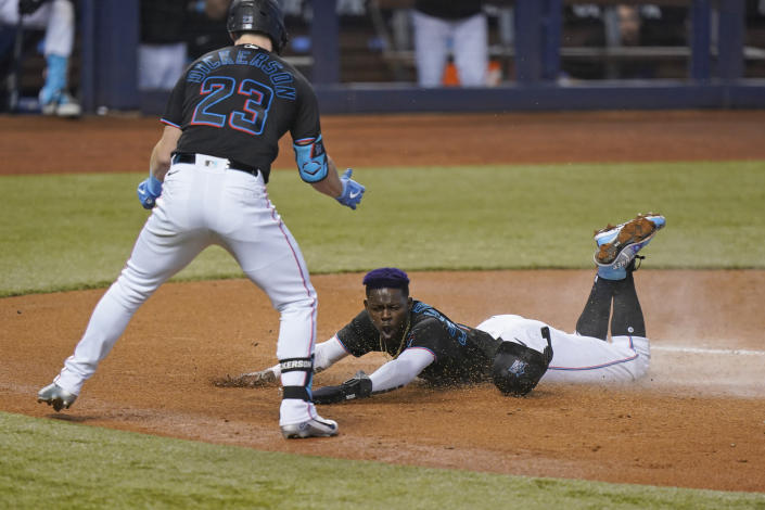Miami Marlins' Corey Dickerson (23) celebrates as Jazz Chisholm Jr. slides into home to score on a sacrifice fly ball hit by Jesus Aguilar during the first inning of a baseball game against the Atlanta Braves, Saturday, June 12, 2021, in Miami. (AP Photo/Wilfredo Lee)