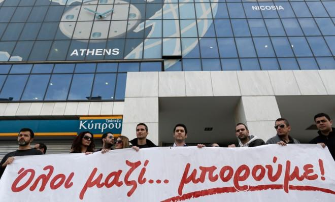 Employees of the Athens, Greece Bank of Cyprus rally in solidarity with the struggling island country.