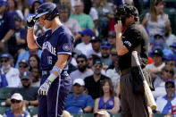 Chicago Cubs' Patrick Wisdom, left, throws his bat after being called out on strikes during the fourth inning of a baseball game against the San Francisco Giants in Chicago, Friday, Sept. 10, 2021. (AP Photo/Nam Y. Huh)