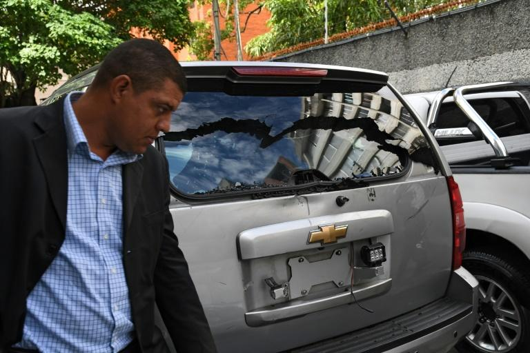 One of Juan Guaido's bodyguards walks next to a damaged vehicle after pro-government supporters allegedly attacked a convoy of opposition lawmakers