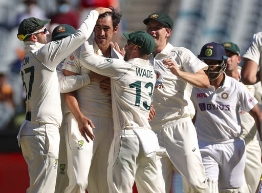 Australia's Mitchell Starc, centre, is congratulated by teammates after dismissing India's Mayank Agarwal, second right, during play on day one of the Boxing Day cricket test between India and Australia at the Melbourne Cricket Ground, Melbourne, Australia, Saturday, Dec. 26, 2020. (AP Photo/Asanka Brendon Ratnayake)