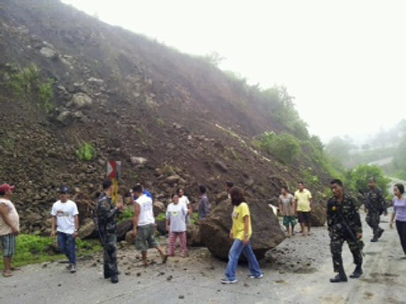 In this photo released by North Cotabato Provincial Office, residents look at boulders that partially blocked a highway after an earthquake in North Cotabato in southern Philippines Sunday, June 2, 2013. A magnitude-5.7 earthquake rattled this province and nearby areas late Saturday, damaging more than 140 houses and several school buildings and setting off a landslide that partially blocked the road, officials said. Dozens of people in the hard-hit North Cotabato villages of Kimadzil and  Kibugtongan, said Hermes Daquipa, a Philippine Institute of Volcanology and Seismology official who joined a government team that surveyed the hilly villages. (AP Photo/North Cotabato Provincial Office)  EDITORIAL USE ONLY, NO SALES