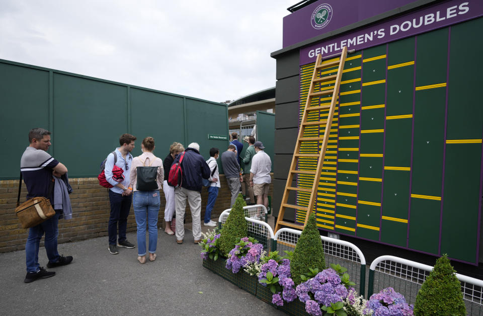 People queue to spectate on Court 17 on day two of the Wimbledon Tennis Championships in London, Tuesday June 29, 2021. Arguably, no country has elevated sport's role in society quite as much as Britain so the absence of crowds for much of the coronavirus pandemic has been a constant reminder, if any were needed, of the cultural toll of COVID-19. The steady return of fans to sports over the past few weeks and the promise of packed-out stadiums very soon provide hope that life is returning to normal in the wake of the rapid rollout of coronavirus vaccines. (AP Photo/Alastair Grant)