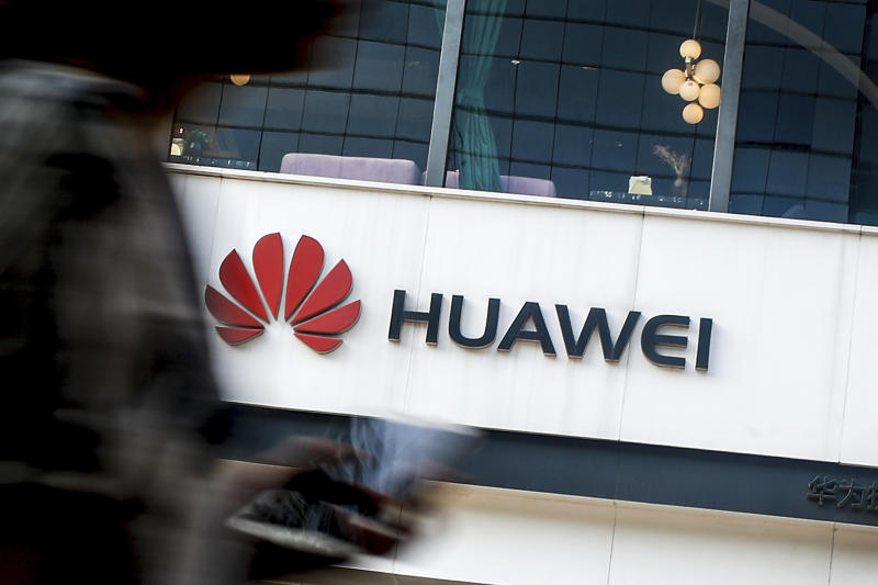 FILE - In this July 30, 2019, file photo a woman walks by a Huawei retail store in Beijing. The U.S. government gave chipmakers and technology companies a 90-day extension to sell products to technology giant Huawei. (AP Photo/Andy Wong, File)