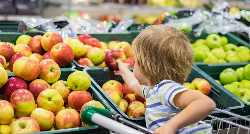 Woolworths offers quiet hour for children and adults with autism and sensory issues. Pictured is a stock image of a child in a trolley grabbing an apple.