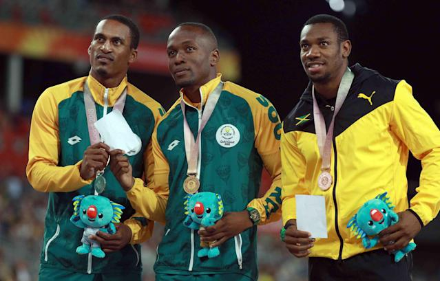 Athletics - Gold Coast 2018 Commonwealth Games - Men's 100m medal Ceremony - Carrara Stadium - Gold Coast, Australia - April 10, 2018. Gold medalist Akani Simbine of South Africa, silver medalist Henricho Bruintjies of South Africa and bronze medalist Yohan Blake of Jamaica pose with medals. REUTERS/Athit Perawongmetha