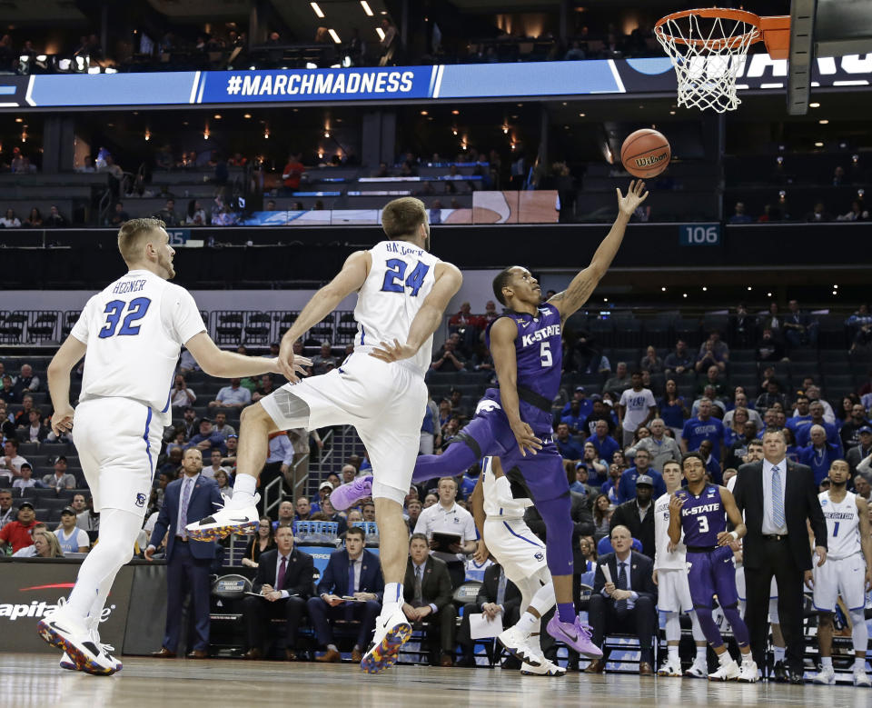 Kansas State's Barry Brown (5) shoots in front of Creighton's Mitch Ballock (24) and Toby Hegner (32) during the first half of a first-round game in the NCAA men's college basketball tournament in Charlotte, N.C., Friday, March 16, 2018. (AP Photo/Gerry Broome)