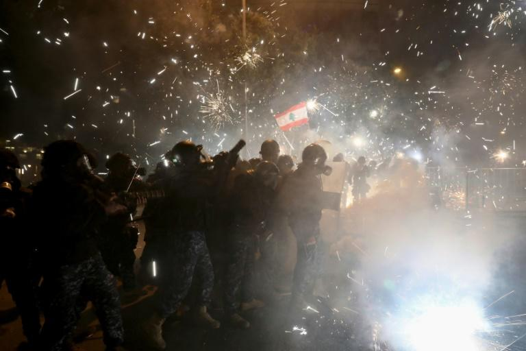 Lebanese security forces react to fireworks hurled  by anti-government protesters in downtown Beirut