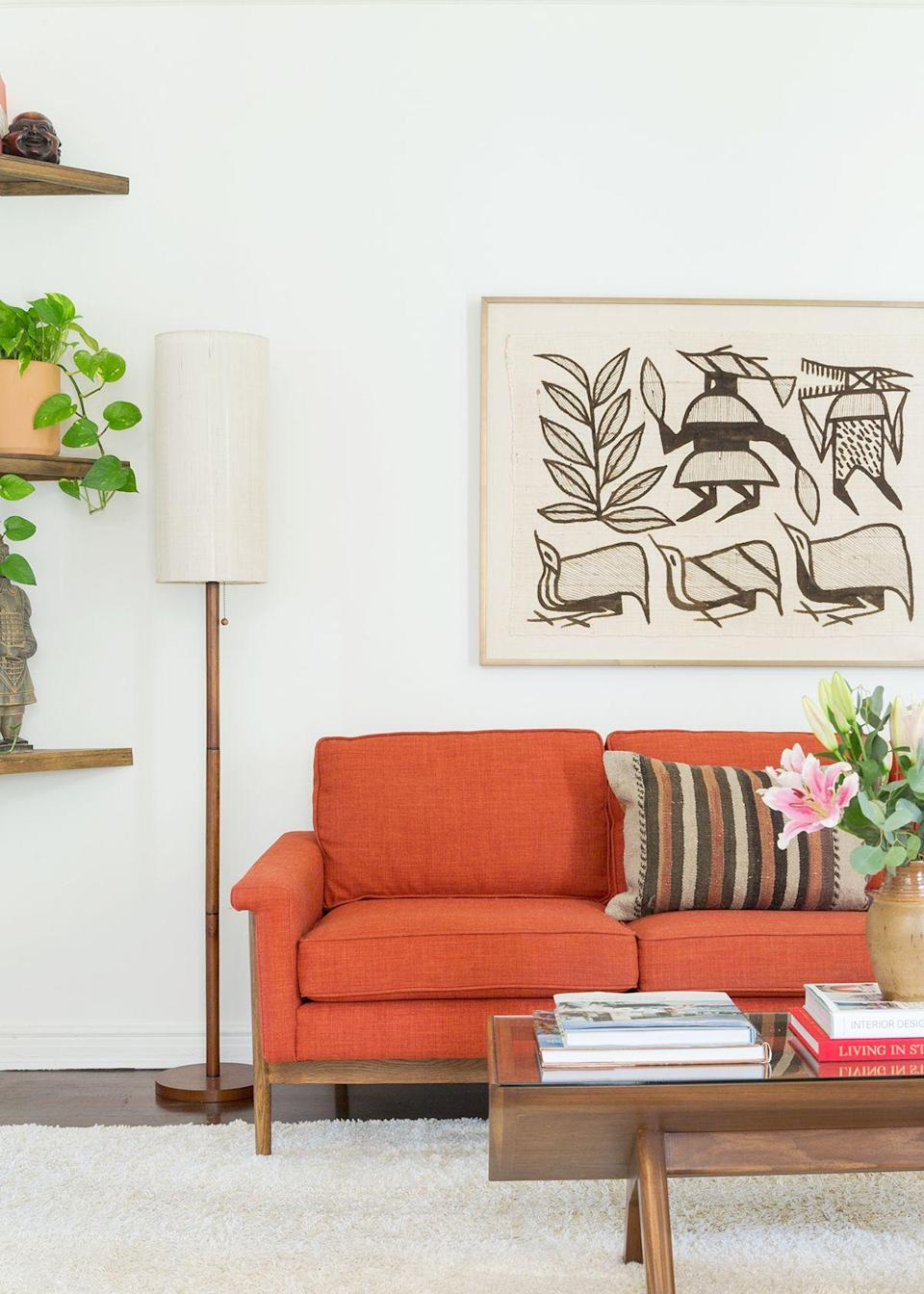 """After selecting the burnt orange sofa, """"the space evolved into an eclectic combination of vintage, handcrafted pieces, and stylish but utilitarian box-store items,"""" says Cheng. The designer made a point to select neutral accessories so as not to compete with the sofa and make the small space feel even smaller, she explained. To make the house feel """"finished,"""" she opted for a collection of truly unique artwork."""
