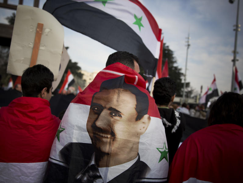 A Syrian demonstrator is wrapped in a Syrian flag carrying the picture of President Assad as they shout pro-government slogans during a demonstration outside the United Nations headquarters in Geneva, Switzerland, Friday Jan. 31, 2014. The first face-to-face meetings between Syria's warring sides in three years were wrapping up Friday, with a patient U.N. mediator struggling to build enough momentum for a more constructive second round to break through the deadly impasse. (AP Photo/Anja Niedringhaus)