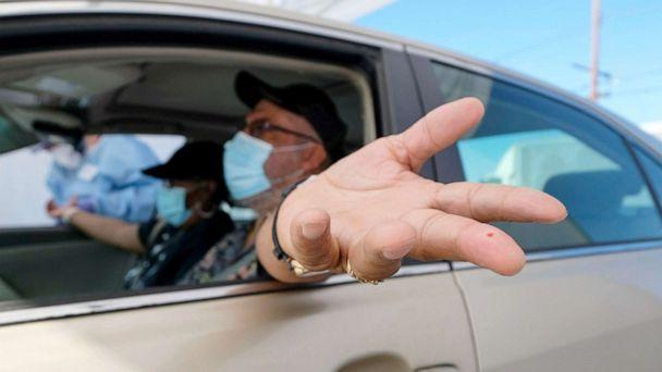 PHOTO: A motorist holds out his hand after having blood drawn at the Southside Church of Christ in Los Angeles, Jan. 18, 2021. (Ringo Chiu/AFP via Getty Images)