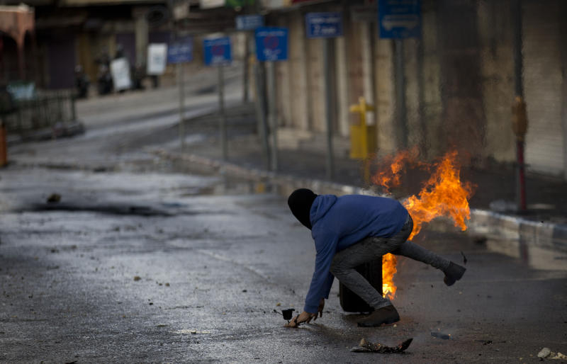 A Palestinian demonstrator kicks a burning tire during a protest in the West Bank city of Hebron, Monday, Dec. 9, 2019. Palestinian residents held a general strike to protest an Israeli plan to build a new Jewish neighborhood in the heart of the West Bank's largest city.    (AP Photo/Majdi Mohammed)