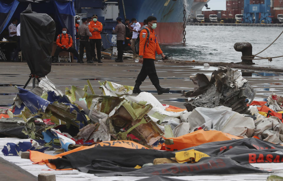 An Indonesian rescue team member walks near debris found in the waters around the location where a Sriwijaya Air passenger jet crashed, at the search and rescue command center at Tanjung Priok Port in Jakarta, Indonesia, Indonesia, Wednesday, Jan. 13, 2021. Divers looking for the crashed plane's cockpit voice recorder were searching in mud and plane debris on the seabed between Indonesian islands Wednesday to retrieve information key to learning why the Sriwijaya Air jet nosedived into the water over the weekend. (AP Photo/Achmad Ibrahim)