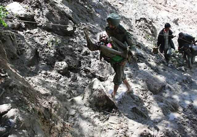 "In this handout photograph released by the Indian Ministry of Defence, Indian military personnel help rescue pilgrims in Uttarakhand state, on June 22, 2013. Relief teams were racing against time June 22 to rescue tens of thousands of stranded people in rain-ravaged northern India as the death toll from flash floods and landslides neared 600. Floods and landslides from monsoon rains have also struck neighbouring Nepal, leaving at least 39 people dead, the Nepalese government said. AFP PHOTO/MINISTRY OF DEFENCE----EDITORS NOTE---- RESTRICTED TO EDITORIAL USE - MANDATORY CREDIT - ""AFP PHOTO/MINISTRY OF DEFENCE"" - NO MARKETING NO ADVERTISING CAMPAIGNS - DISTRIBUTED AS A SERVICE TO CLIENTS -----"