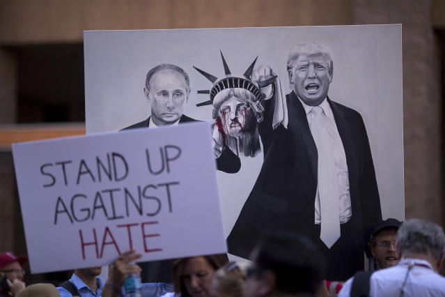 <p>Anti-President Donald Trump demonstrators hold a painting of Russian president Vladimir Putin and Trump outside the Phoenix Convention Center before a rally by Trump on August 22, 2017 in Phoenix, Arizona. (David McNew/Getty Images) </p>