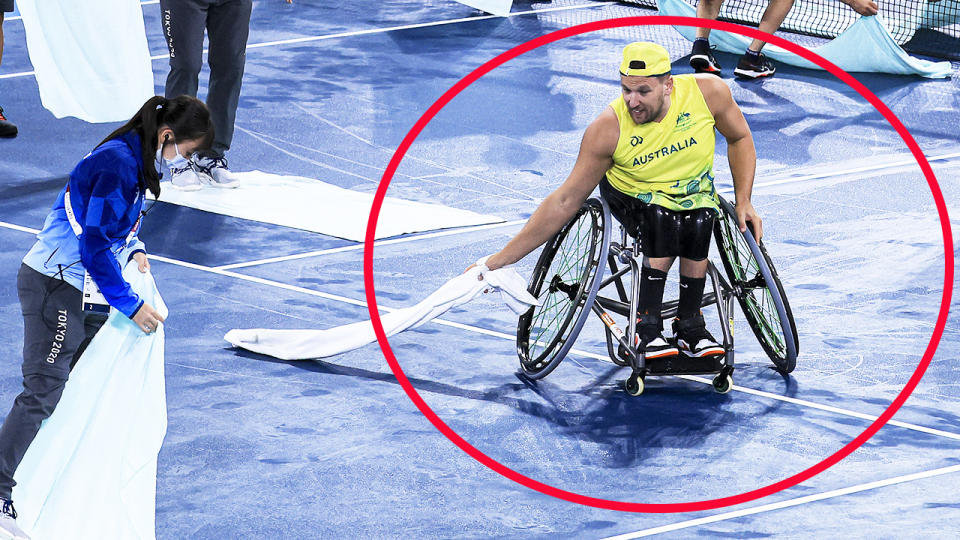 Dylan Alcott, pictured here helping volunteers dry the court at the Paralympics.