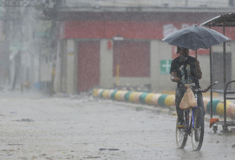 A man rides his bicycle under the rain brought by Hurricane Iota, in La Lima, Honduras, Tuesday, Nov. 17, 2020. Hurricane Iota tore across Nicaragua on Tuesday, hours after roaring ashore as a Category 4 storm along almost exactly the same stretch of the Caribbean coast that was recently devastated by an equally powerful hurricane. (AP Photo/Delmer Martinez)