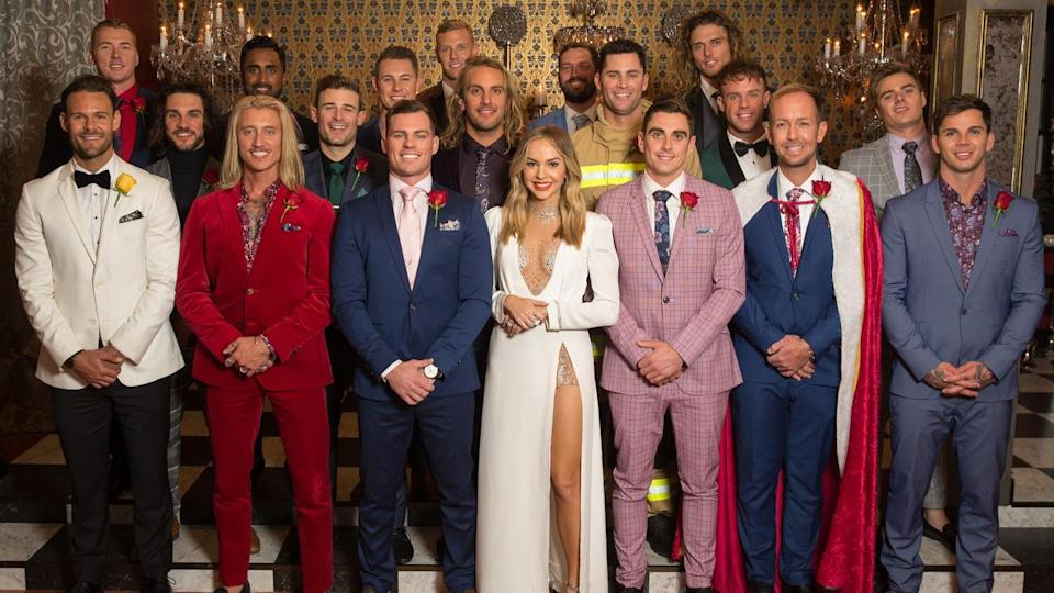 Bachelorette star Angie Kent wearing a white dress surrounded by male contestants in various different coloured suits