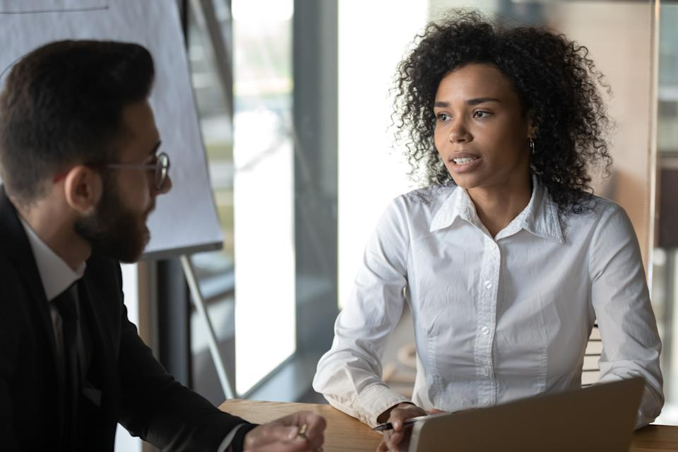 Multiracial business partners met in office sit at desk negotiating focus on american businesslady talking to client make profitable proposition, job interview process HR manager and applicant concept
