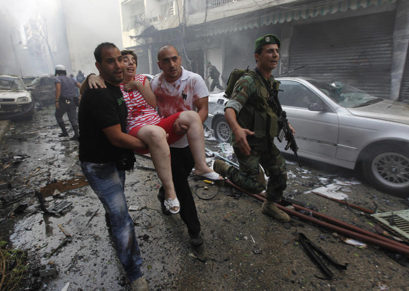 An injured woman is carried away by civilians from the scene of an explosion in the mostly Christian neighborhood of Achrafiyeh, Beirut, Lebanon, Friday Oct. 19, 2012. Lebanese Red Cross and security officials say a car bomb in east Beirut has killed at least eight people and wounded dozens in the worst blast the city has seen in years, coming at a time when Lebanon has seen a rise in tension and eruptions of clashes stemming from the civil war in neighboring Syria. (AP Photo/Hussein Malla)