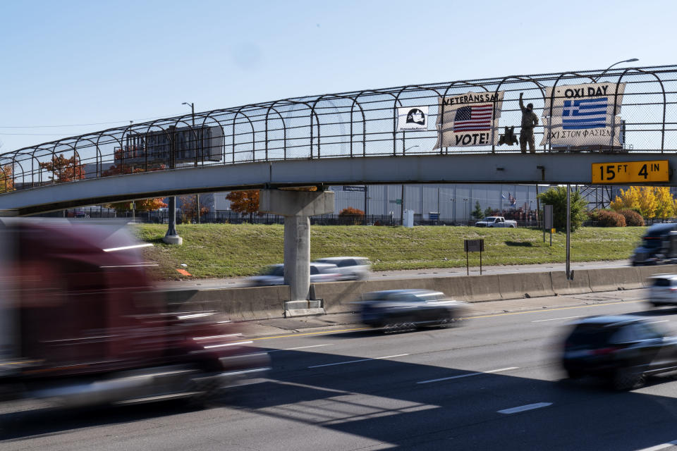 An Iraq and Afghanistan war veteran, who did not give his name, stands on a highway overpass with signs encouraging motorists to vote in Hamtramck, Mich., Wed, Oct. 28, 2020. Early voting numbers, nearly 90 million by Saturday morning, suggest 2020 will shatter voter turn-out records. Trump has alleged without evidence that wide-spread absentee voting will lead to fraud. (AP Photo/David Goldman)