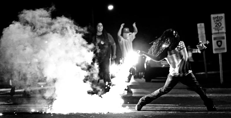 Edward Crawford Jr. returns a tear gas canister fired by police who were trying to disperse protesters in Ferguson, Missouri, on  Aug. 13, 2014. (Robert Cohen/St. Louis Post-Dispatch/AP)