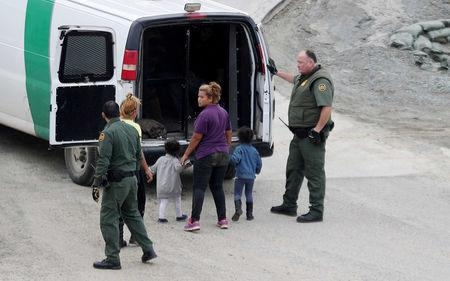 FILE PHOTO: U.S. CBP officials detain a migrant woman and children after they crossed illegally from Mexico to the U.S. as seen from Tijuana