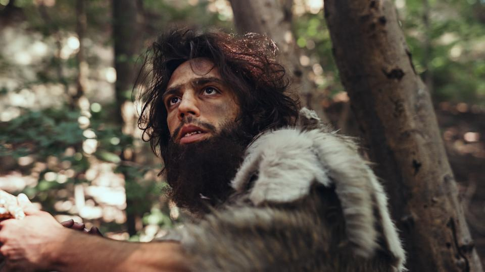 Close-up Portrait of Primeval Caveman Wearing Animal Skin and Fur Hunting with a Stone Tipped Spear in the Prehistoric Forest. Prehistoric Neanderthal Hunter Ready to Throw Spear in the Jungle