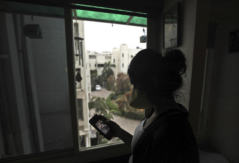 "In this Tuesday, March 24, 2020 photo, an Indian girl wearing a face mask as a precaution from coronavirus watches a video on the WhatsApp app in New Delhi, India. With the pandemic starting to gain a foothold in the region, social media are rife with bogus remedies, tales of magic cures and potentially hazardous medical advice. Experts are urging caution and say the ""coronavirus infodemic"" could have disastrous consequences. (AP Photo/Manish Swarup)"