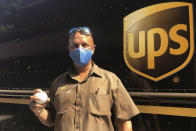 UPS driver Derek Reynolds poses with a foul ball gift, Friday, Sept. 18, 2020, in Alameda, Calif. (AP Photo/Janie McCauley)