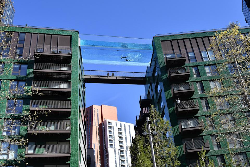Models swim in a transparent acrylic swimming pool bridge that is fixed between two apartment blocks at Embassy Gardens next to the new US Embassy in south-west London on April 22, 2021. - A world first, the transparent 25-metre-long outdoor pool, known as the Sky Pool, will allow residents to swim from one building to the other, 10 storeys above the ground. (Photo by Justin TALLIS / AFP) (Photo by JUSTIN TALLIS/AFP via Getty Images)