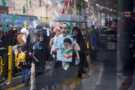 An Iranian woman carries a picture of Iran's Supreme Leader Ayatollah Ali Khamenei during a ceremony to mark the 40th anniversary of the Islamic Revolution in Tehran