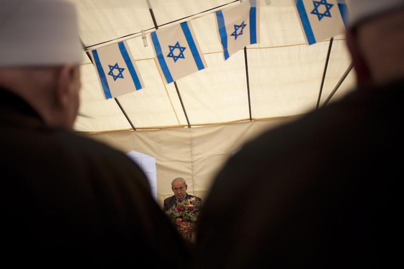"Israel's Prime Minister Benjamin Netanyahu, center, attends the holiday of Nabi Shoaib, the Prophet Jethro, during a cultural event with members of the country's Druse minority in the Druse village of Julis, northern Israel, Thursday, April 25, 2013. Israel shot down a drone Thursday as it approached the country's northern coast, the military said. Suspicion immediately fell on the Hezbollah militant group in Lebanon. The incident was likely to raise already heightened tensions between Israel and Hezbollah, a bitter enemy that battled Israel to a stalemate during a monthlong war in 2006. Netanyahu, who was in northern Israel at the time of the incident, said he viewed the infiltration attempt with ""utmost gravity."" (AP Photo/Ariel Schalit)"