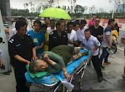 A woman is helped as she is sent to hospital after being pulled out by a diver from the sunken ship in Jianli, Hubei province, China, June 2, 2015. REUTERS/Stringer