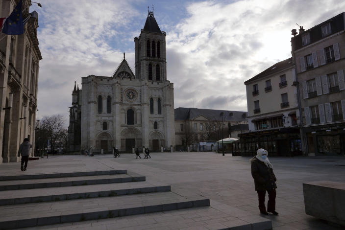 A woman walks past the Saint-Denis Basilica, a burial place for French kings entombed, north of Paris, Monday, Jan. 25, 2021. Many people lining up for vaccines in the Paris suburb are particularly grateful for the injections. The surrounding region is the poorest in mainland France, with 130 languages spoken and the country's highest rise in mortality last spring. (AP Photo/Christophe Ena)