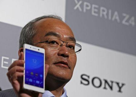 Sony Mobile Communications Inc President and CEO Totoki poses with Sony's new Xperia Z4 smartphone after a news conference in Tokyo